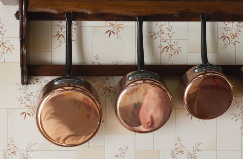copper pots hanging on wall
